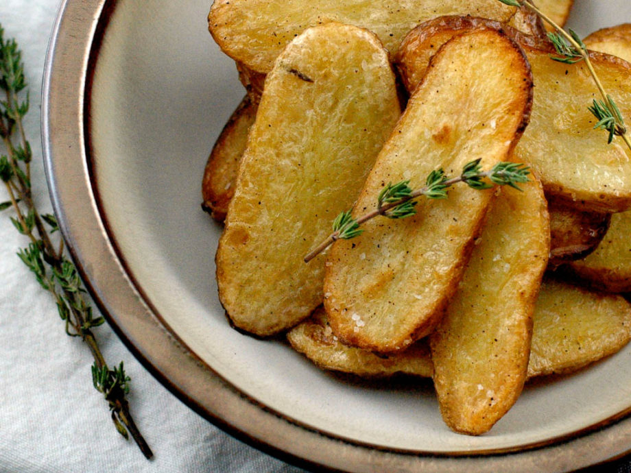 golden slices of salt and vinegar fingerling potatoes in a bowl with thyme