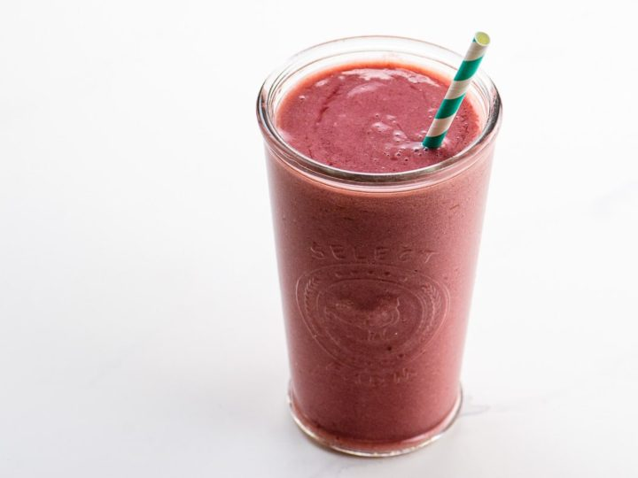 strawberry shortcake smoothie in a glass with a straw