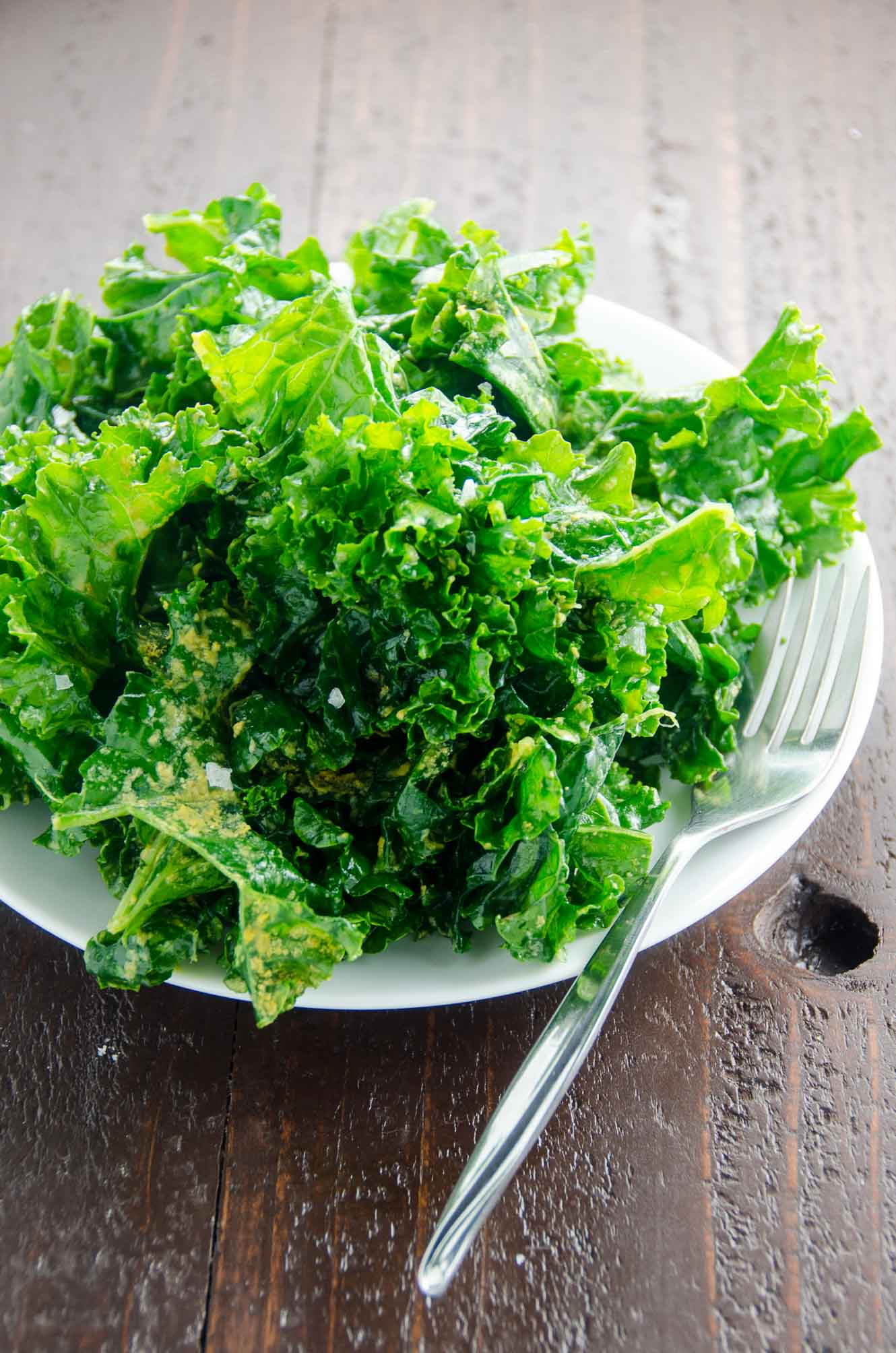 massaged kale salad with nutritional yeast (vegan) on a white plate