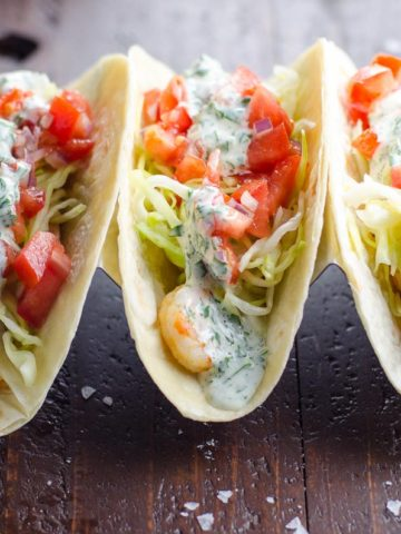 three garlic shrimp tacos on a wood table with cilantro sauce