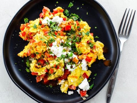 overhead shot of scrambled eggs cooked with onion and red bell pepper, sprinkled with cotija cheese, cilantro, and hot sauce, on a black plate on a white background