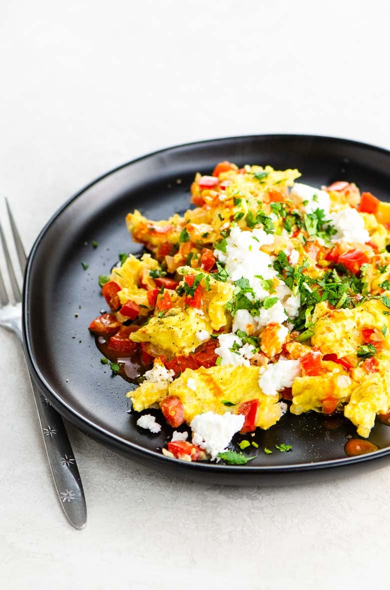 scrambled eggs cooked with onion and red bell pepper, sprinkled with cotija cheese, cilantro, and hot sauce, on a black plate on a white background