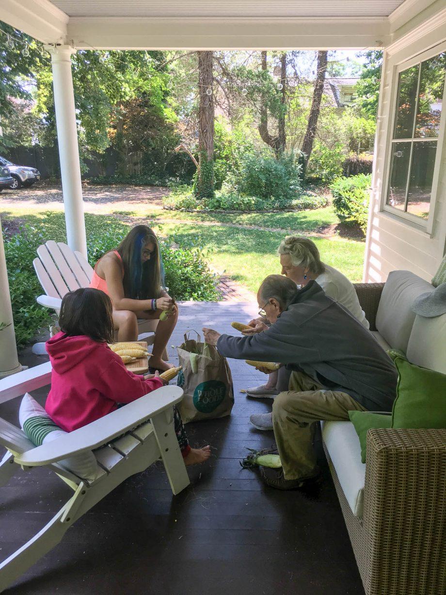 family shucking corn on a porch
