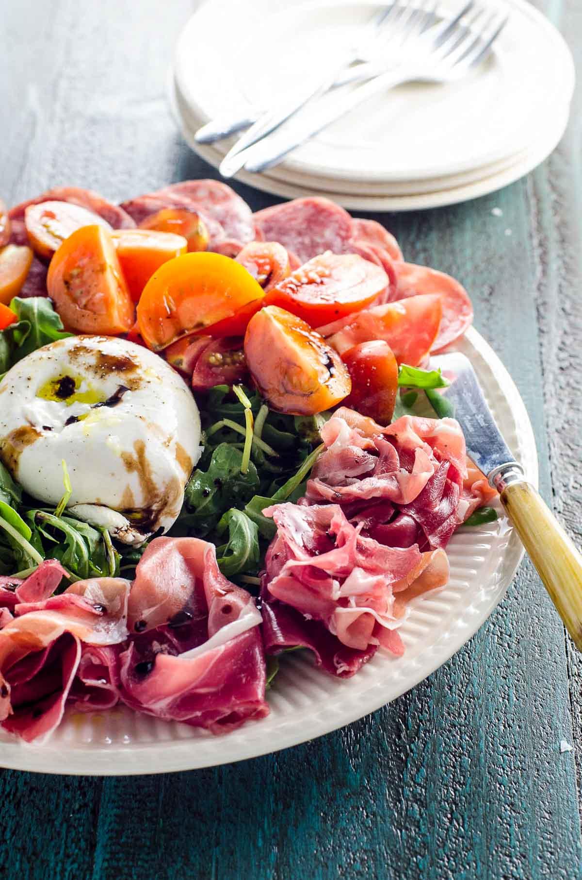burrata platter with soppressata, prosciutto, arugula, tomatoes, olive oil, balsamic glaze, and flaky salt