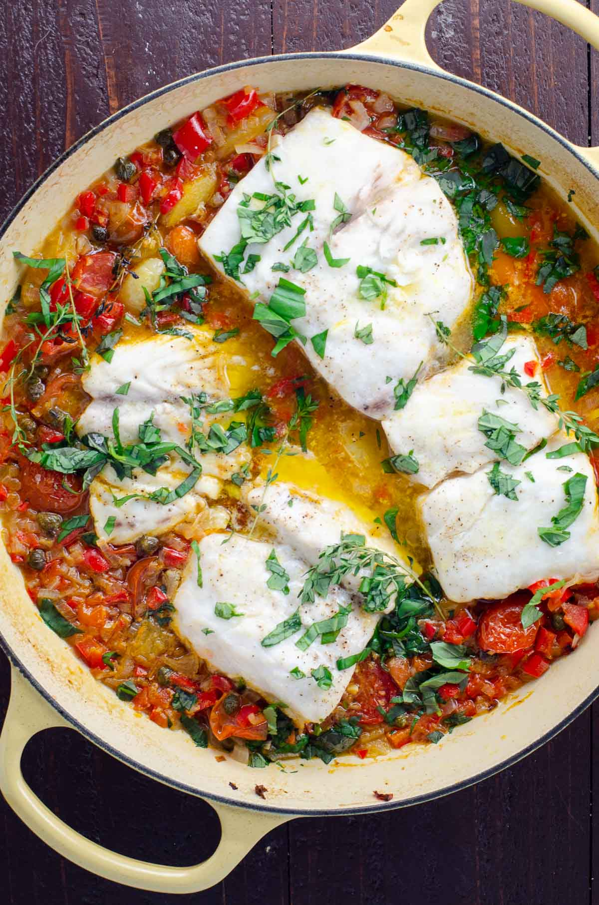 striped bass with brightly colored vegetables in a cast iron braiser