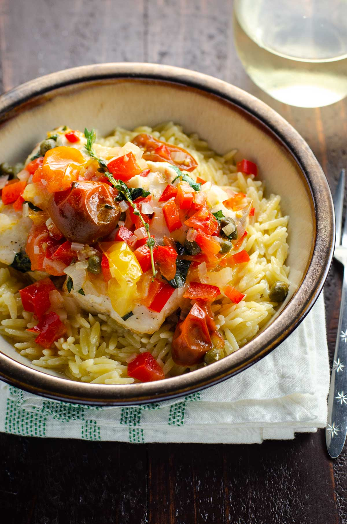 a bowl with orzo, striped bass, and vegetables