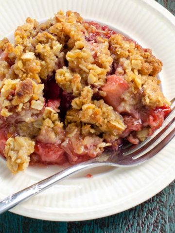 strawberry rhubarb crisp on a plate with a fork