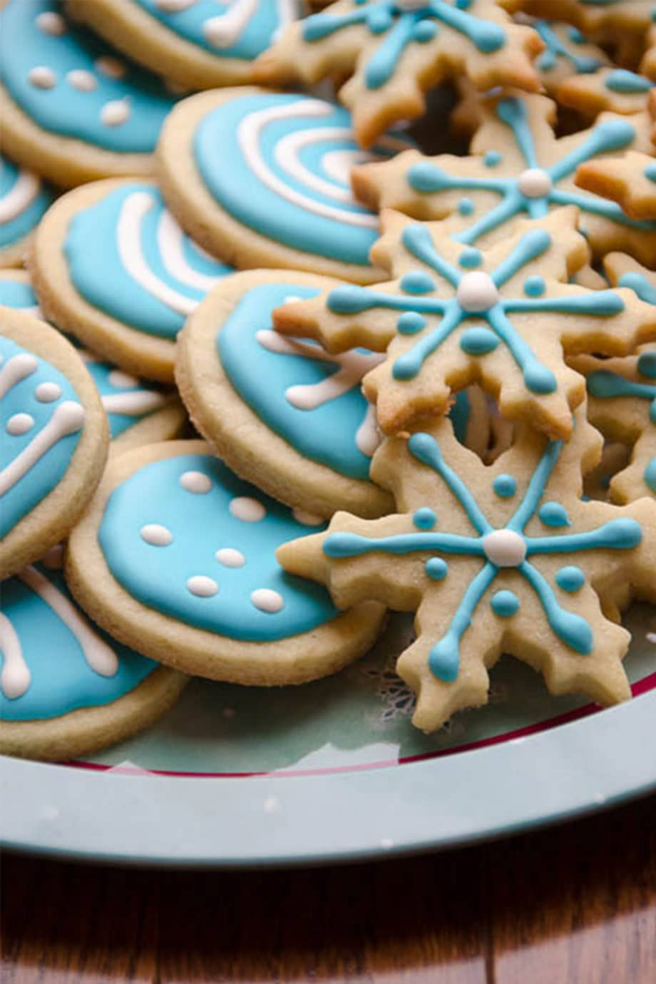 a plate of christmas cookies with blue and white icing