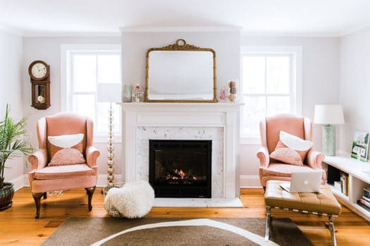Project January cozy living room with fireplace, pink wingback chairs, laptop, mantle mirror