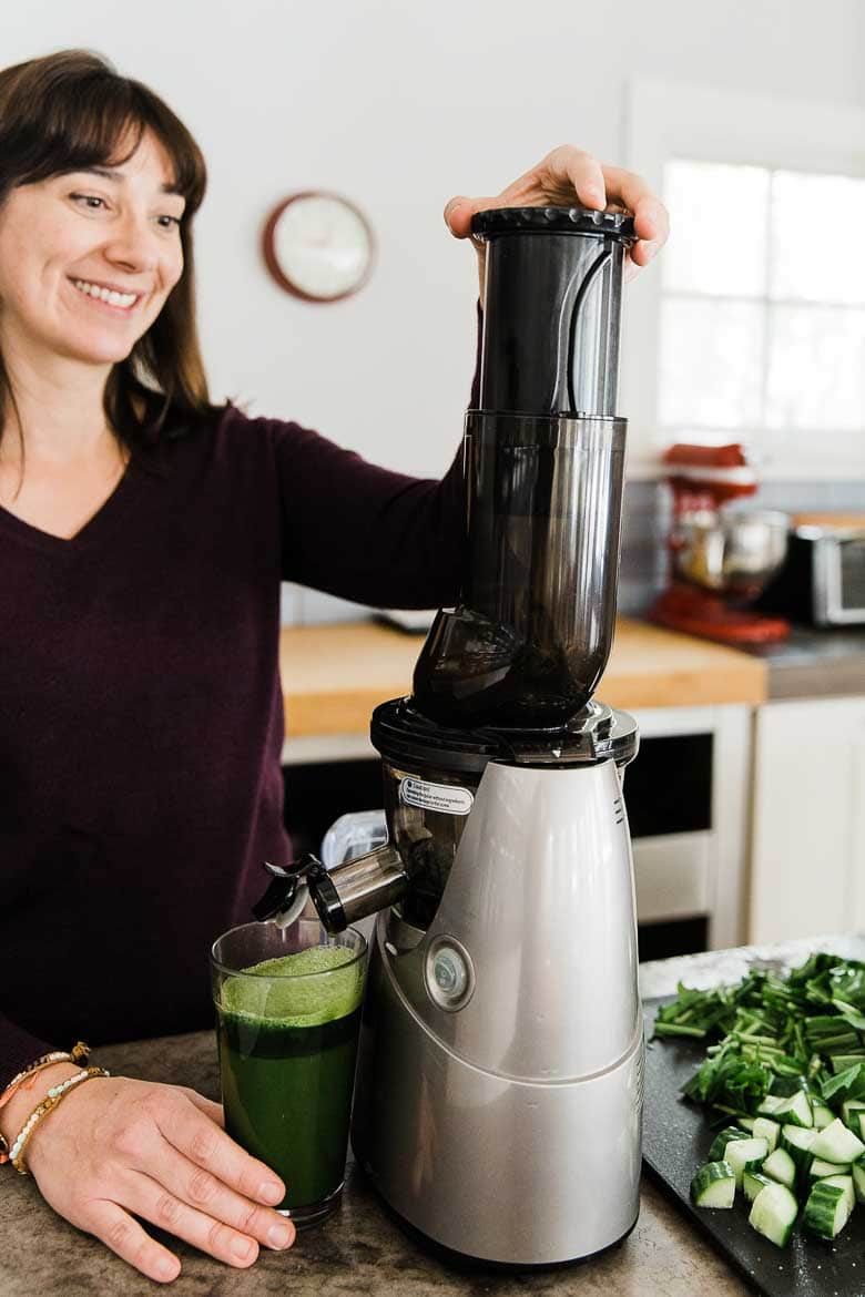 Carolyn Gratzer Cope making green juice with a juicer