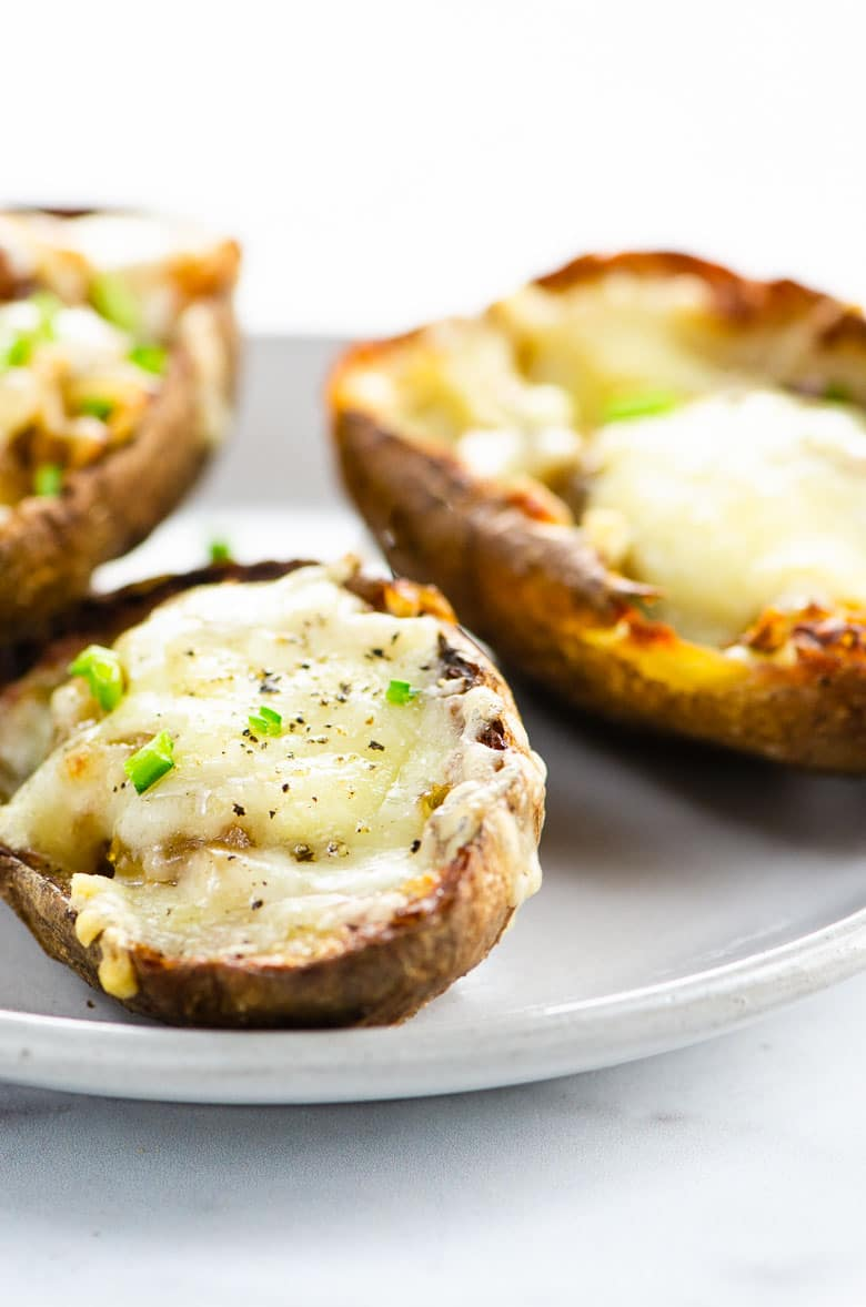 closeup of three french onion soup potato skins on a small gray plate on a marble background