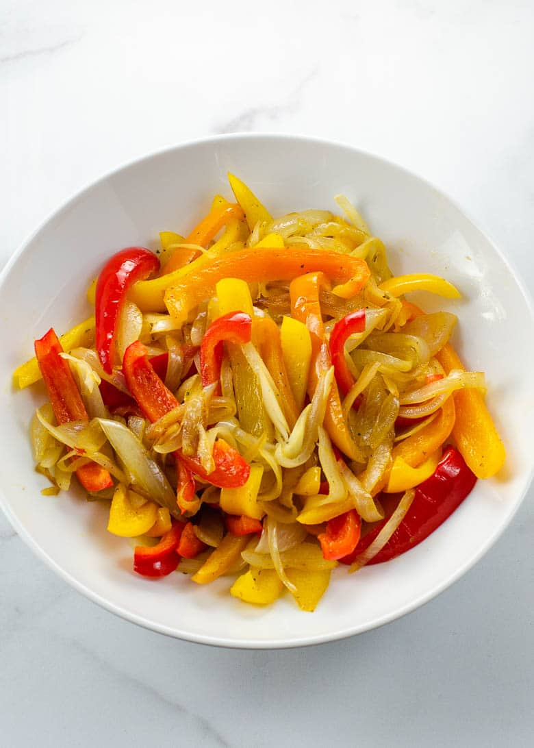 white bowl on marble with sautéed red, yellow, and orange bell peppers and onions