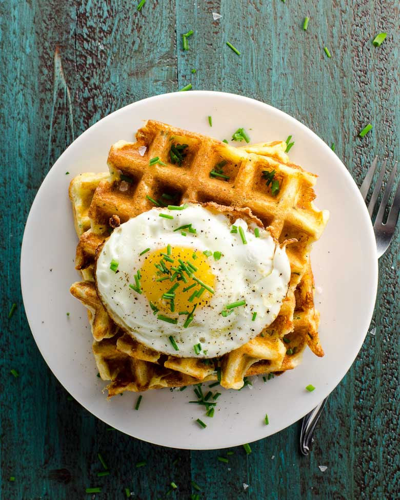fried-egg topped waffles on a white plate against a blue wood background