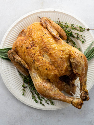 simple roast chicken on a platter with thyme and sage