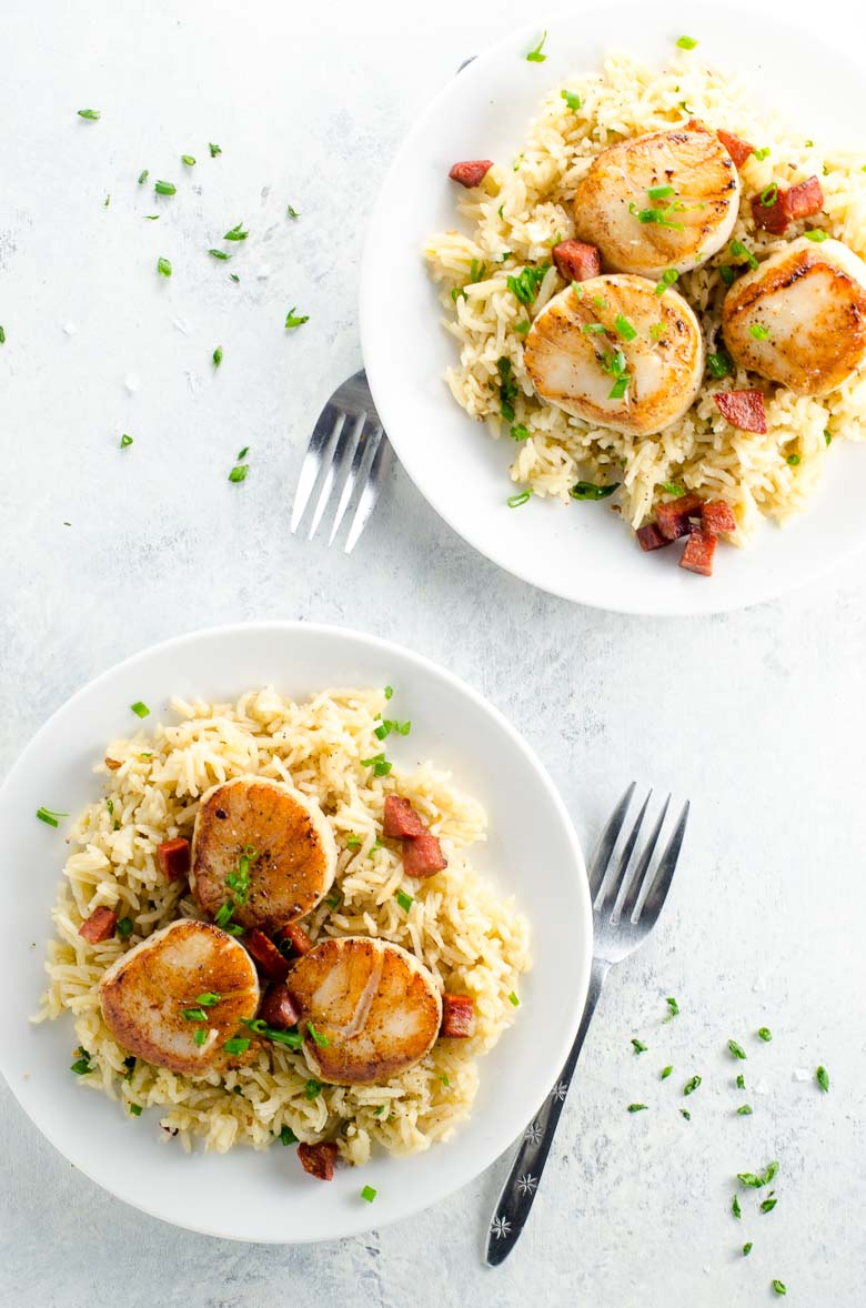 Two plates of scallops and chorizo over rice pilaf