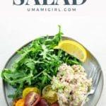 Tuna salad, rainbow tomatoes, arugula, and a lemon wedge on a grey plate on a light colored background