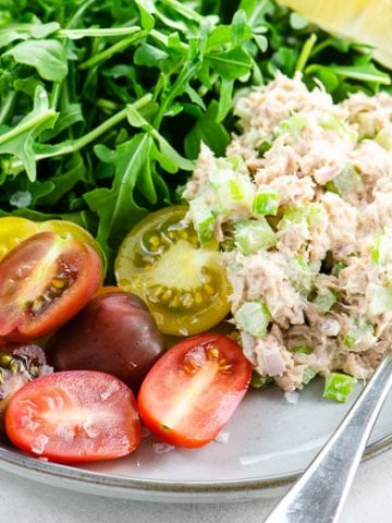 Tuna salad, rainbow tomatoes, arugula, and a lemon wedge on a grey plate on a light colored background
