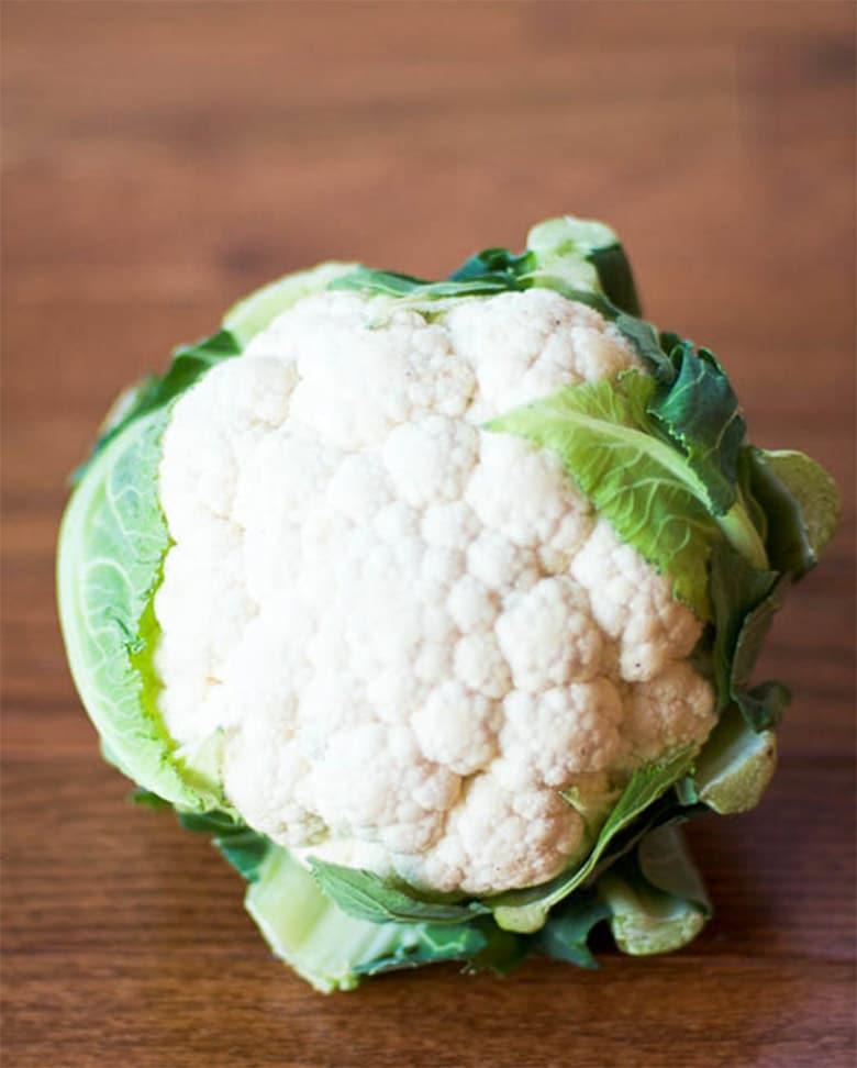 Whole head of cauliflower on wood background