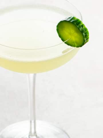 gin gimlet in a coupe glass with cucumber slice garnish on a white background