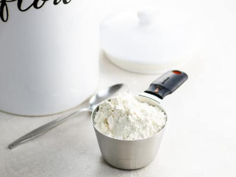 Heaping cup of flour with spoon and jar of flour in background