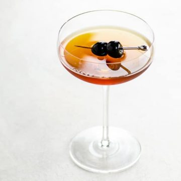 Coupe glass on a white background with a golden brown cocktail and two skewered luxardo cherries