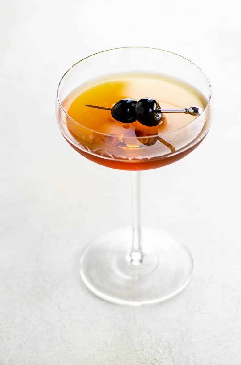 Coupe glass on a white background with a golden brown cocktail and two skewered luxardo cherries for a classic Manhattan cocktail recipe