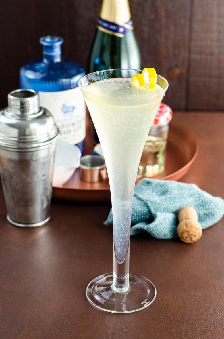French 75 cocktail in a champagne flute with a lemon twist garnish, on a dark background, with ingredients behind the glass