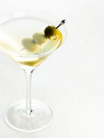 dirty martini with three skewered olives in a martini glass on a light background