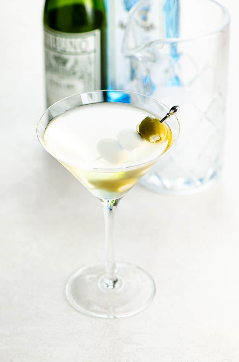 dirty martini with three skewered olives in a martini glass on a light background with blurred bottles of sapphire gin and dry vermouth behind the glass