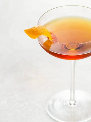 brown cocktail in a coupe glass garnished with an orange twist on a light background