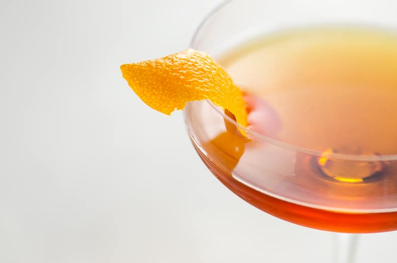 closeup of a martinez cocktail with an orange twist