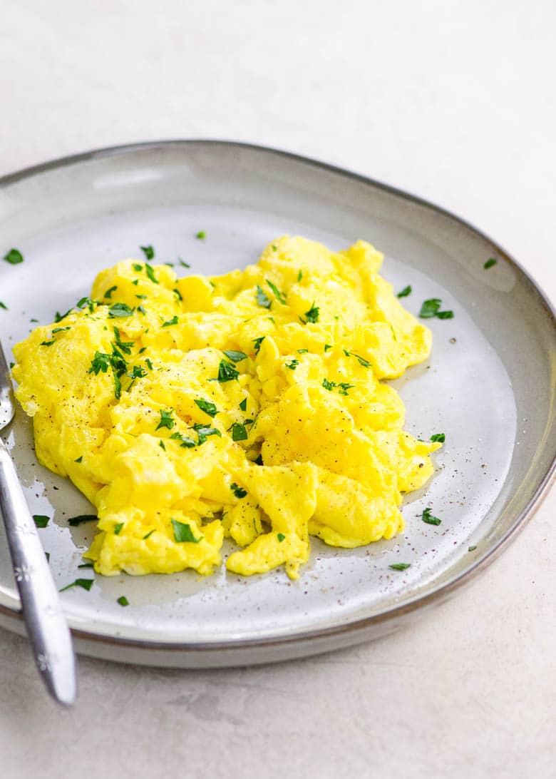 scrambled eggs with parsley and a fork on a grey plate on a light background