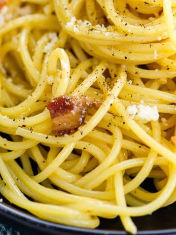 closeup of spaghetti carbonara on a black plate