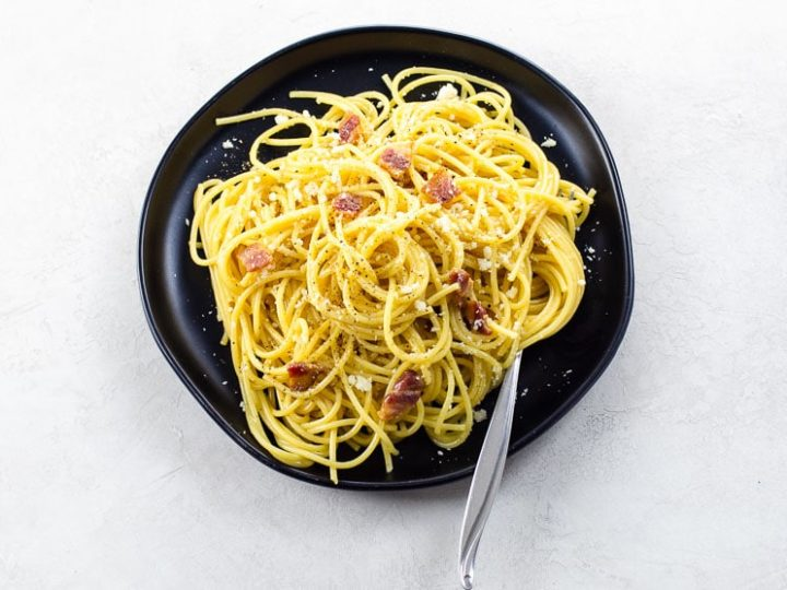 spaghetti alla carbonara on a black plate with a fork on a light background