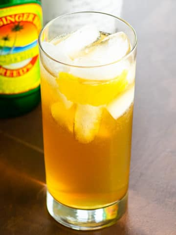 an amber-colored cocktail in a highball glass with bottles of ginger beer, apple brandy, and cardamaro blurred behind, on a brown background