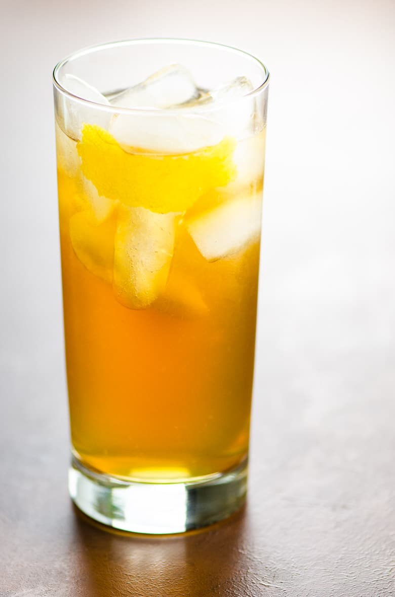 an amber-colored cocktail in a highball glass on a brown background