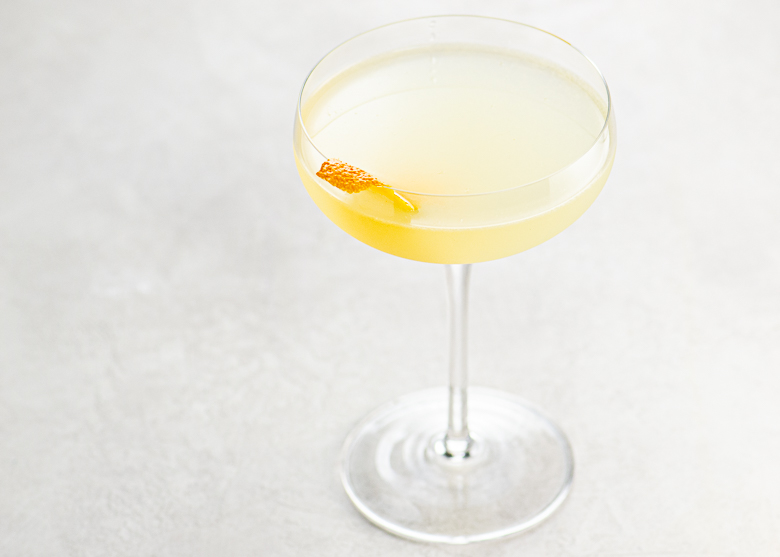 light orange tinted cocktail in a couple glass, garnished with an orange twist, on a light background