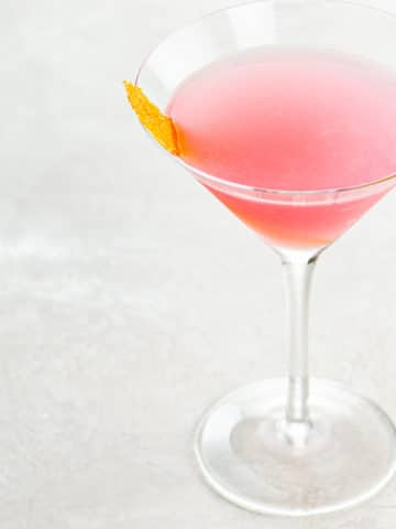 A pink cosmopolitan cocktail garnished with an orange twist in a cocktail glass on a light background