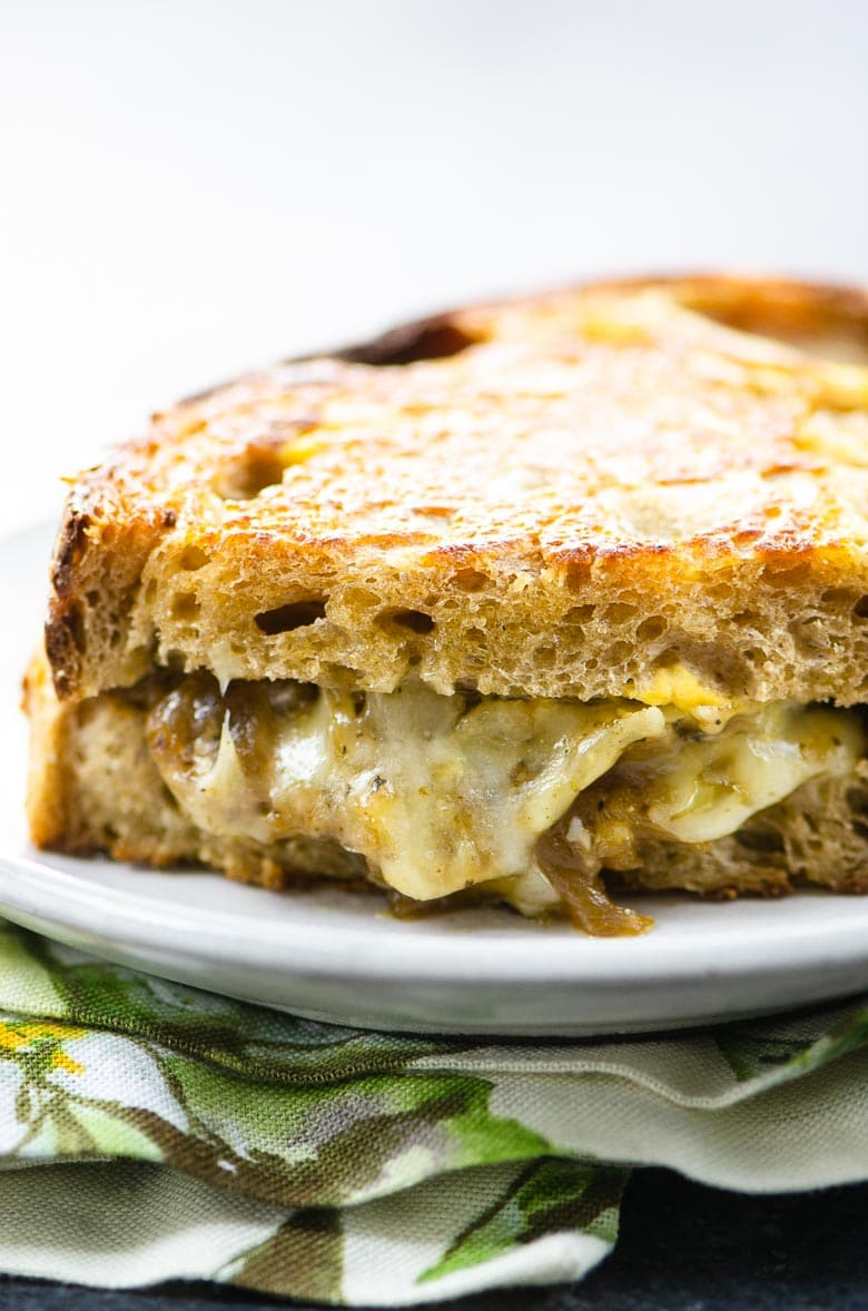 grilled cheese with onions on a plate on a napkin