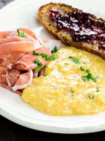french scrambled eggs on a plate with prosciutto and toast
