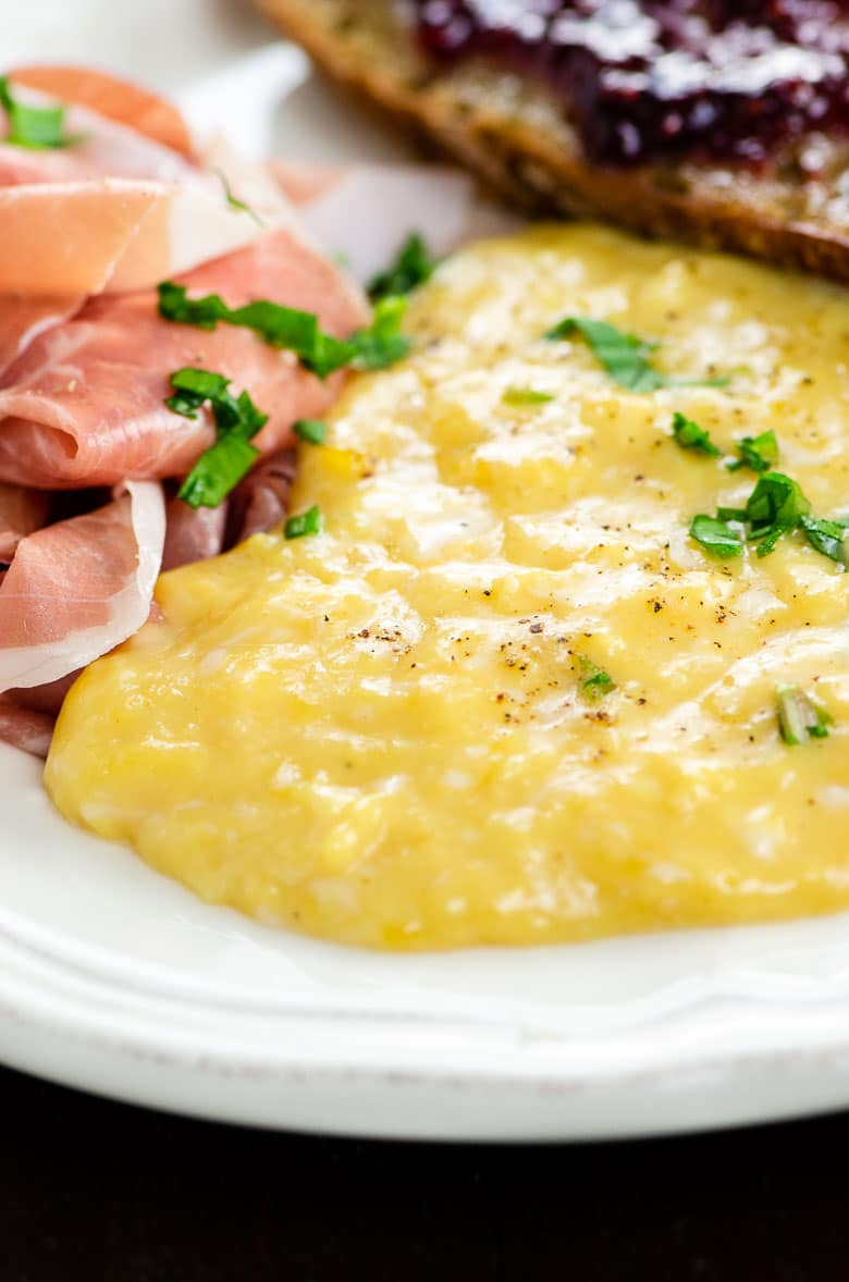 custardy soft scrambled eggs on a plate with prosciutto and toast