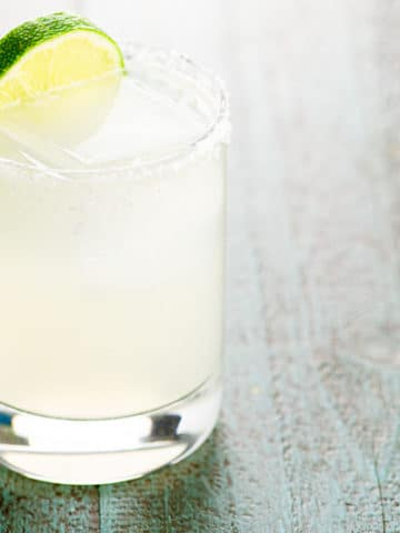 margarita in a rocks glass garnished with a slice of lime on a blue wood background