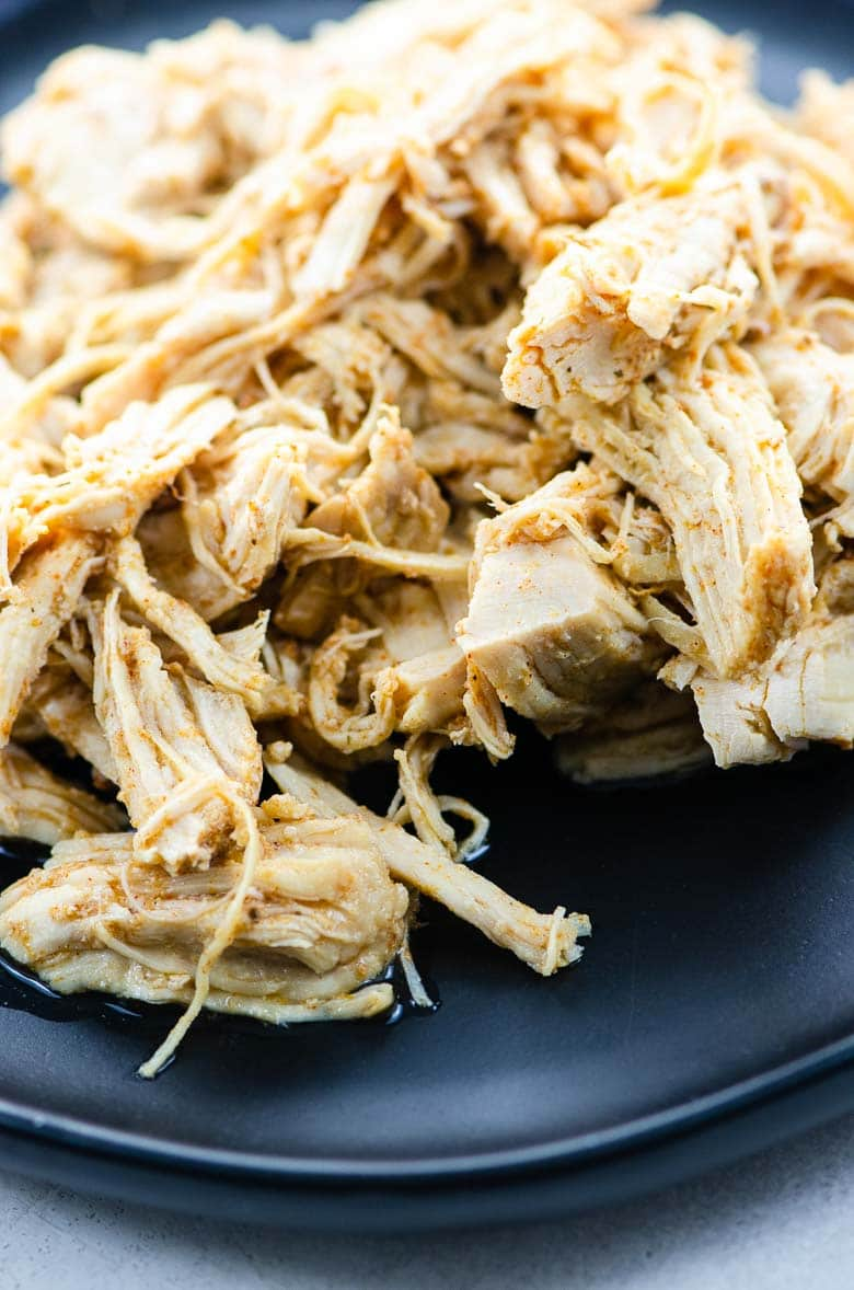 closeup of shredded chicken on a black plate