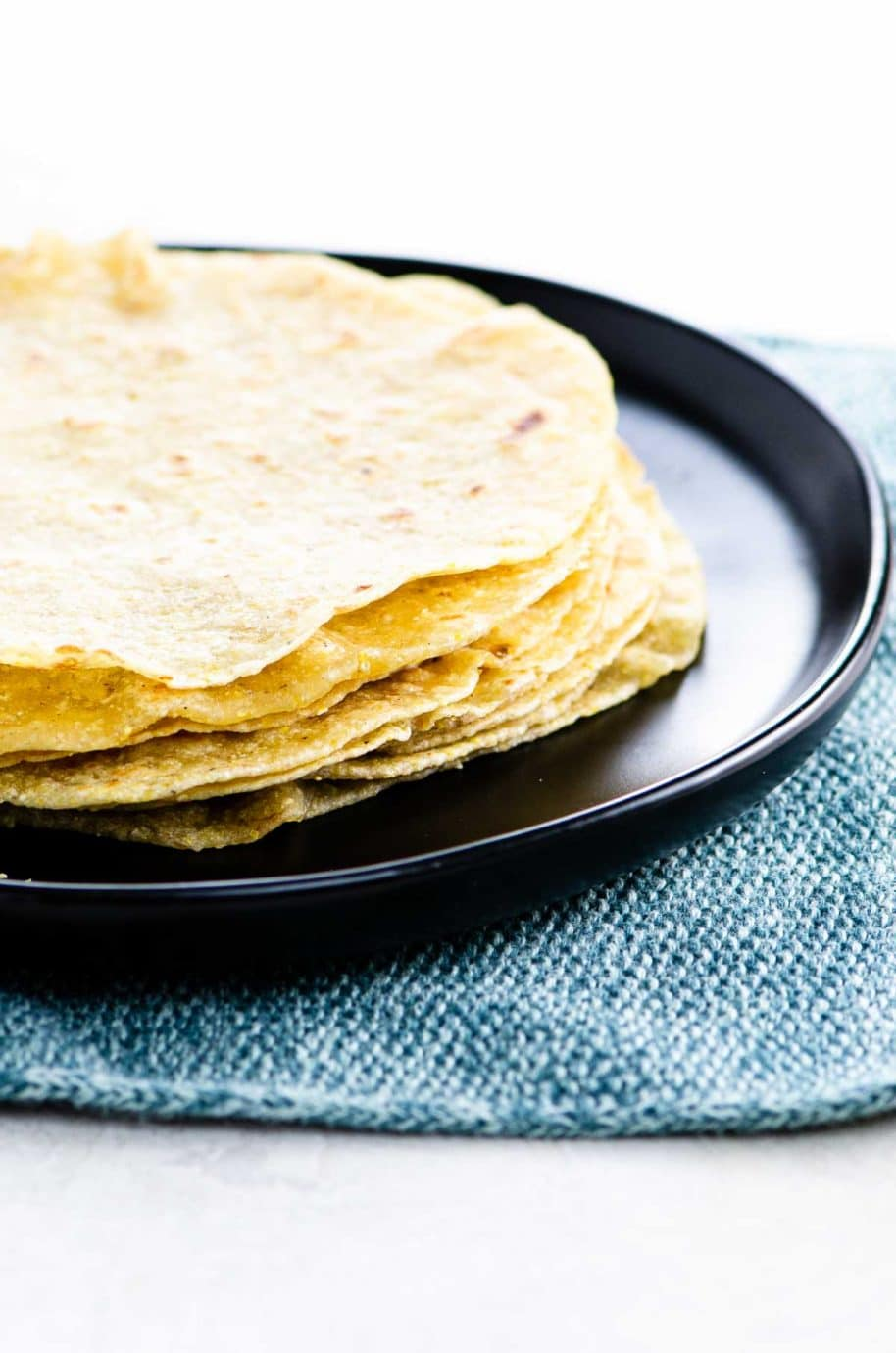 a stack of soft corn tortillas on a black plate on a blue textile background