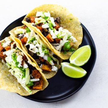 three tacos with two lime wedges on a black plate