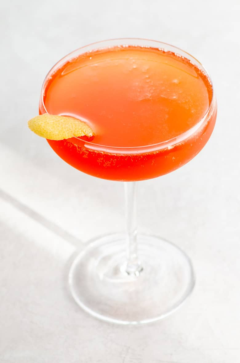 an aperol cocktail in a coupe glass garnished with a grapefruit twist on a light background