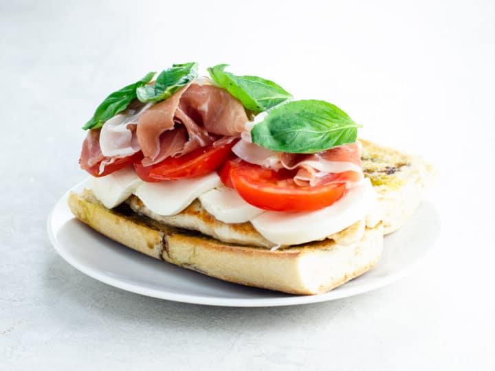 chicken caprese sandwich open face on a plate