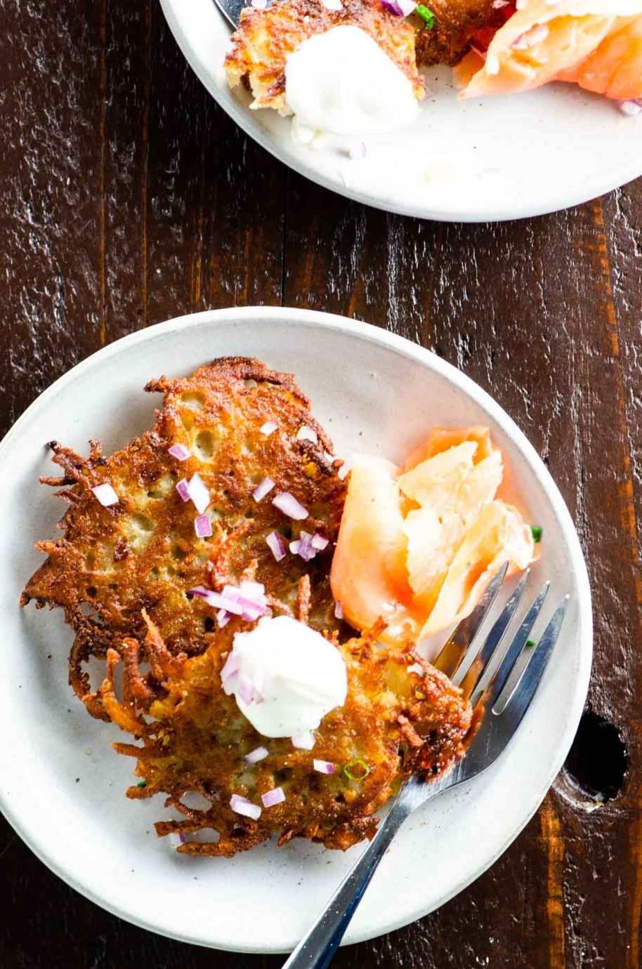 potato pancakes, smoked salmon, and sour cream on plates