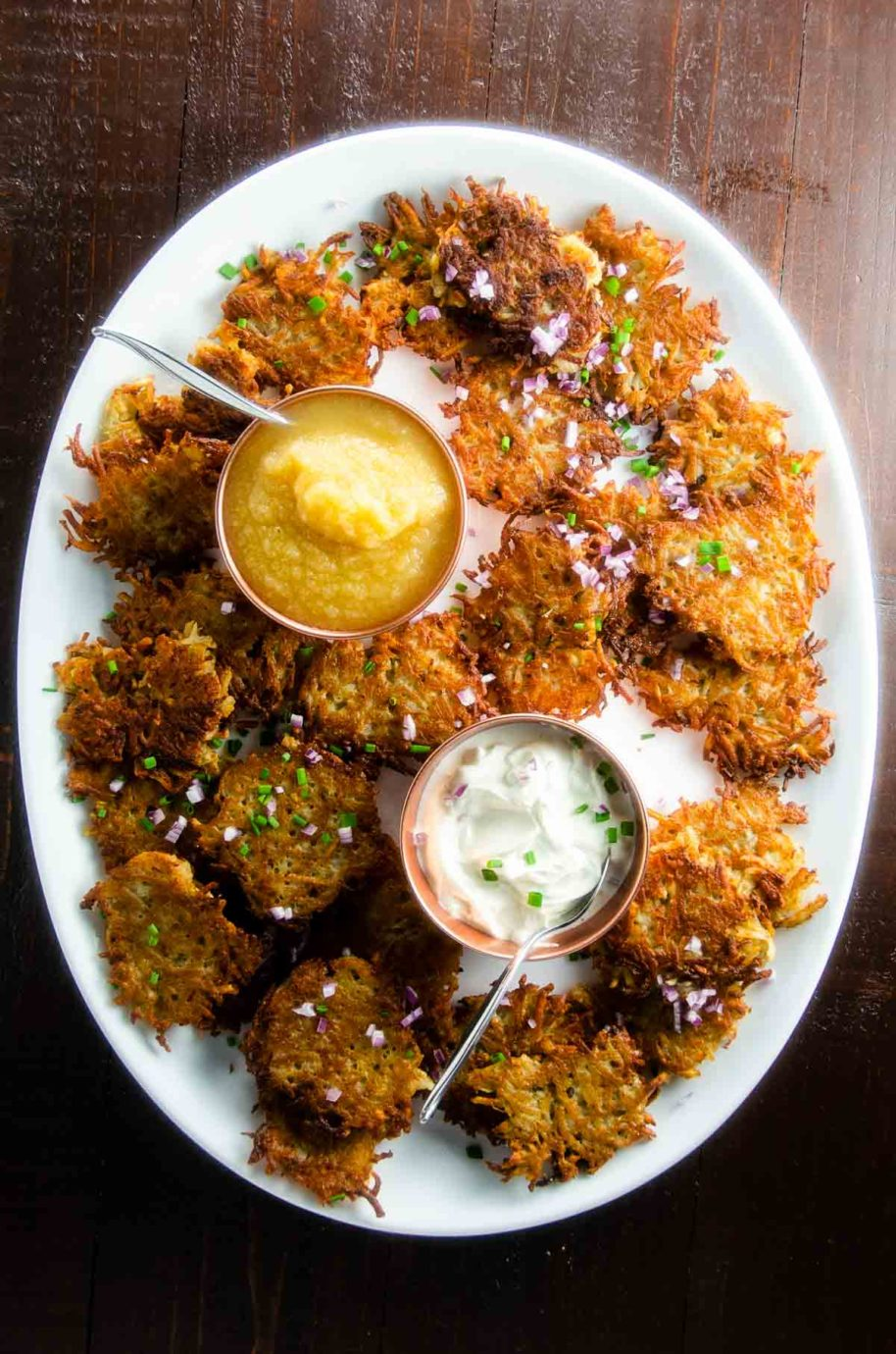 platter of easy potato pancakes with applesauce and sour cream
