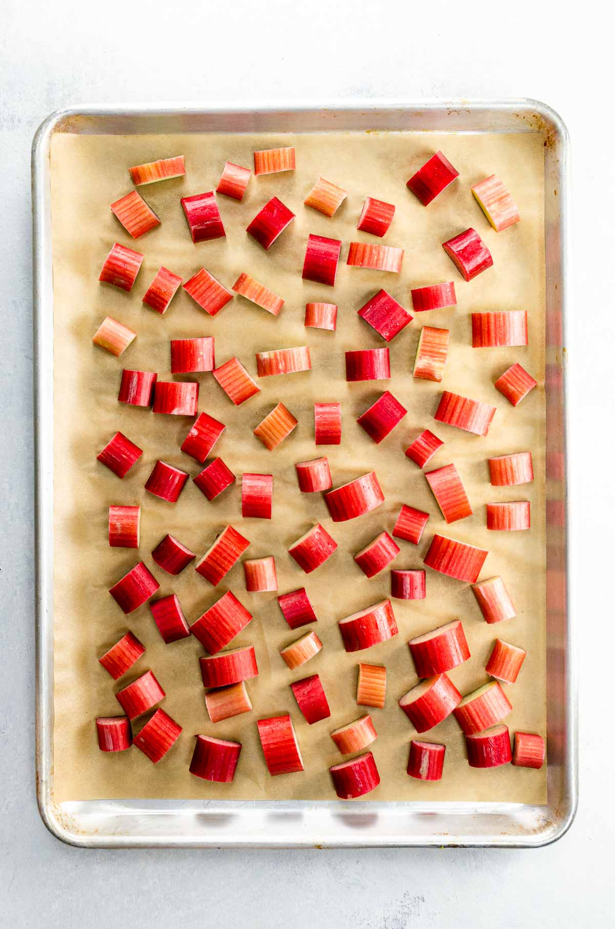 rhubarb slices on a parchment-lined, rimmed baking sheet